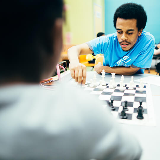 BGCMA leader and youth playing chess