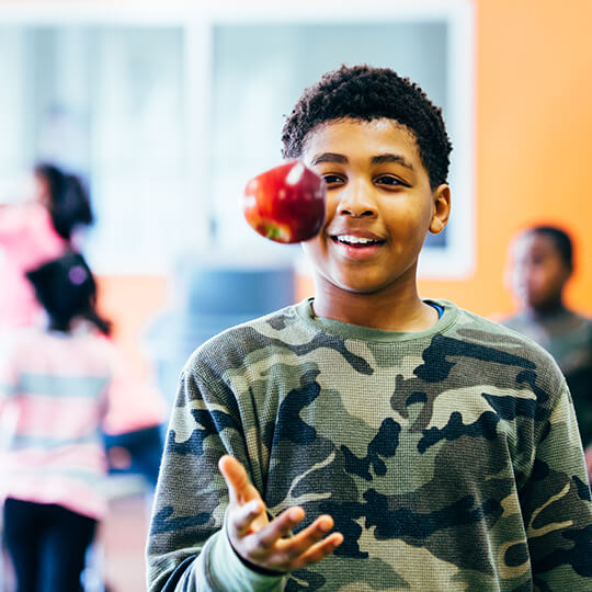 BGCMA youth holding up healthy apple