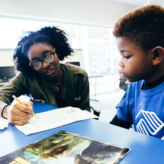 BGCMA teen helping youth with homework